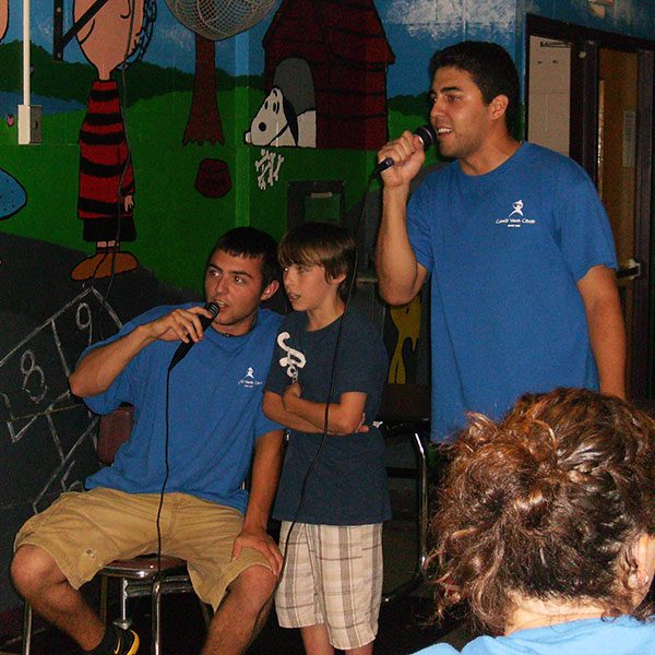 Coloie Youth Center Summer Camp Counselors singing with young boy
